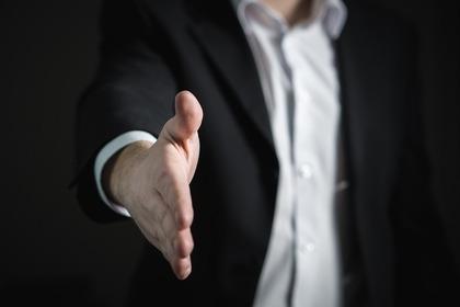 手を差し出す黒いスーツ姿の男性画像