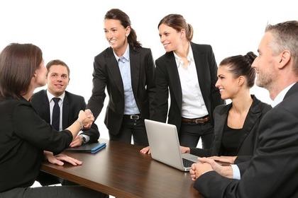 黒いスーツ姿の男女数名が会議で握手を交わす画像