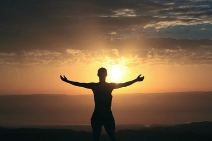夕日に向かって手を広げる人