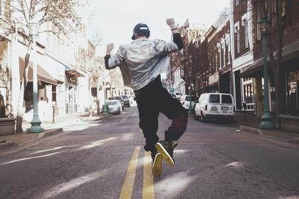 路上で軽やかに踊る男性