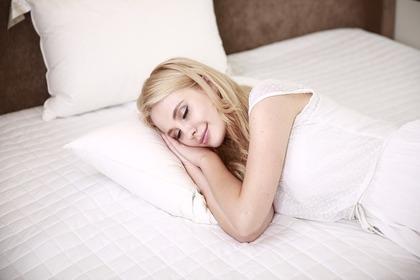 ベッドで寝る金髪の女性