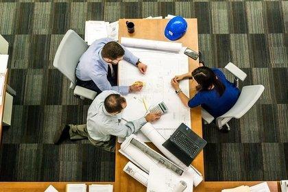 テーブルを挟みオフィスで打ち合わせをする男女画像