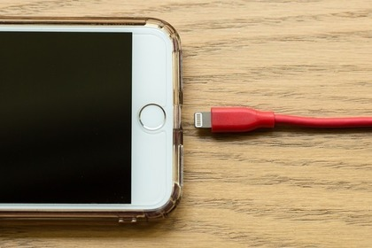 iPhoneと赤色のLightningケーブル