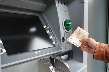 ATMにお札を入れようとしている人