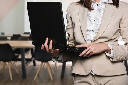 会議室でパソコンを持ち立つスーツ姿の女性画像