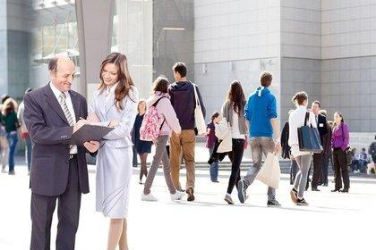 公共の場でスーツを着て資料を見ながら会話する男女画像