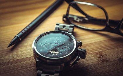 木製のテーブルの上に置かれた腕時計と眼鏡とボールペン画