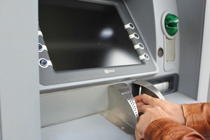 ATMに暗証番号を打ち込んでいる人