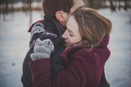 雪の中で彼氏に抱きつく女性