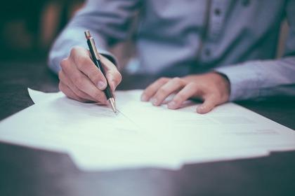 ボールペンで手紙を書く男性
