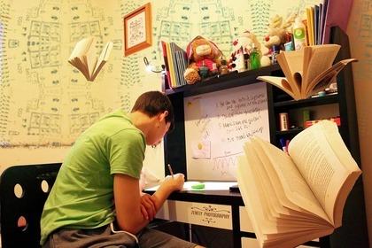 自宅の机で必死に勉強する少年