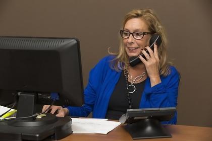 パソコンを操作しながら電話をする女性