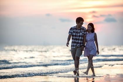 手を繋いで砂浜を歩くカップル