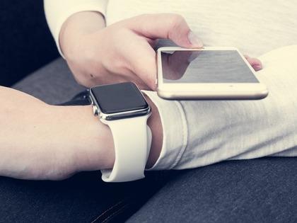 iPhoneとAppleWatchを操作する人