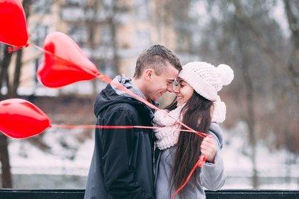 ハートの風船を持って抱きしめ合うカップル