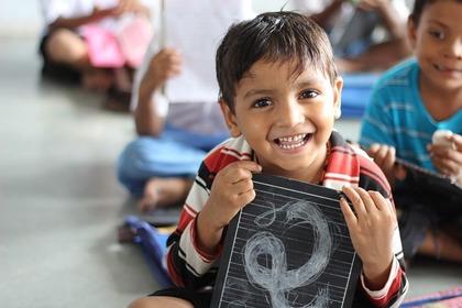 黒板を持って笑うインドの男の子