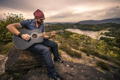 岩の上でギターを弾く男性