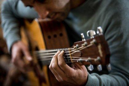 ギターを抱えて弾く男性