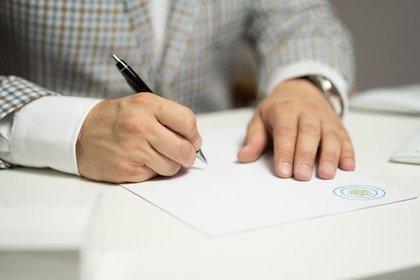 用紙にサインをするスーツ姿の男性