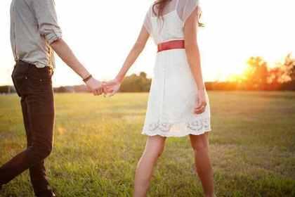手を繋いで原っぱを歩くカップル