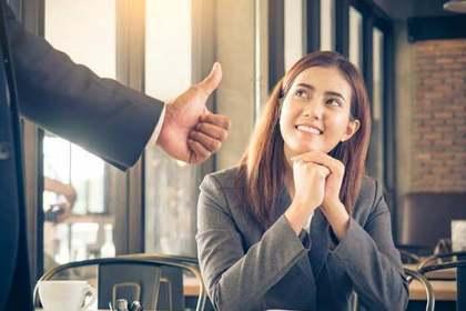 座ったスーツ姿の女性に親指を立てるスーツ姿の男性画像