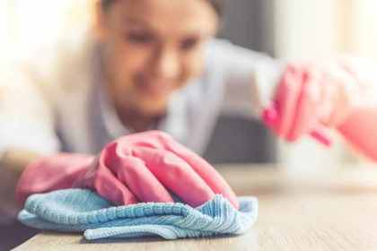 机を拭く女性