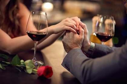 レストランで手を繋ぐ男女