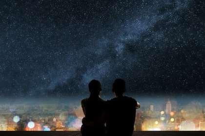 星空と夜景を見る男女