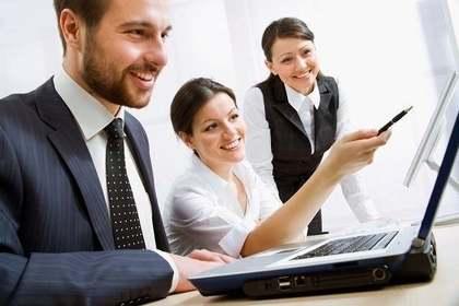 仕事中に同じパソコンを見る3人の男女画像