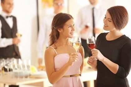 立食パーティーで会話する女性画像