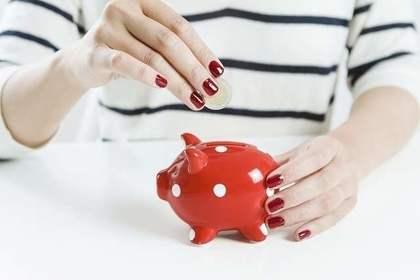 赤い豚の貯金箱に貯金をする様子