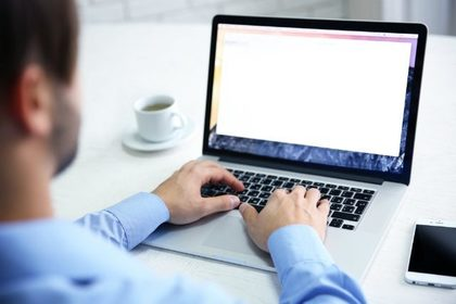 コーヒーが置かれたデスクでパソコンを打つワイシャツを着た男性画像