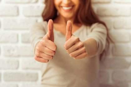 親指を立てるポーズをする女性