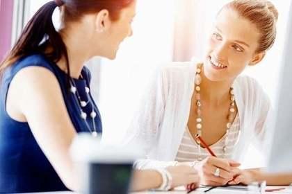 隣同士に座り書類に記入しながら会話する女性画像