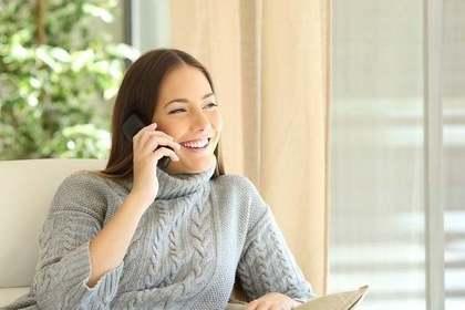 グレーのセーターを着て電話をする女性画像