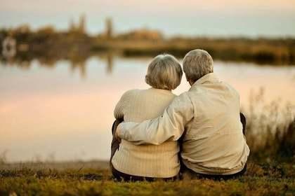 川辺で寄り添う年配の夫婦