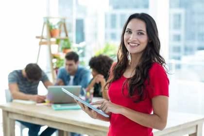 オフィスで赤いTシャツを着て微笑む女性画像