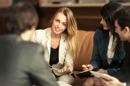 スーツ姿でソファーに座り話し合う数人の男女画像