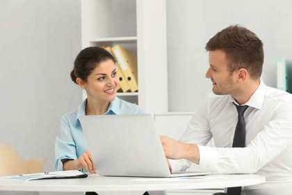 同じテーブルに腰掛け目を見て話す仕事中の男女画像
