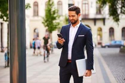 書類と携帯を持ち立つスーツ姿の男性画像