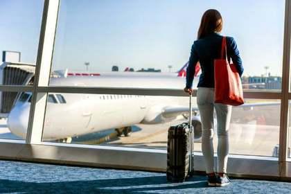 キャリーケースを持ち空港に立つ女性画像