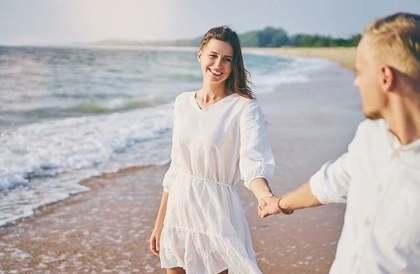 海辺で手をつなぐ男女