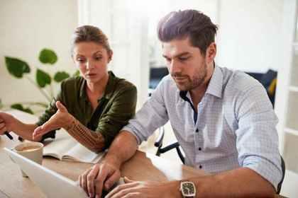 腕まくりをしてパソコンを打つ男性に話しかける女性画像