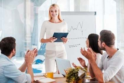 会議でプレゼンする女性に拍手する社員画像