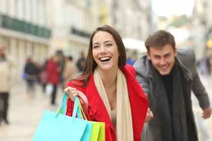 男性の手を引くショッピング中の女性