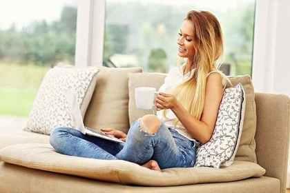 自宅でリラックスしながらパソコンを見る女性