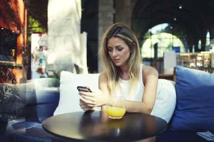 テーブルでiPhoneを操作している女性