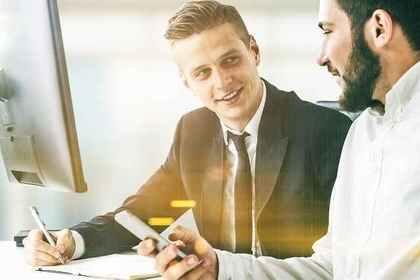 携帯を持つ男性と筆記具を持つ男性が会話する画像