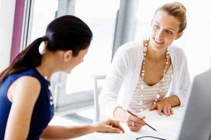 筆記具を持ち会話する2人の女性画像