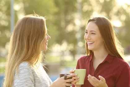 カップを手に談笑する2人